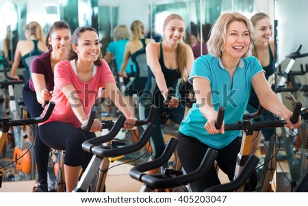 Positive females of different age training on exercise bikes together in modern fitness club