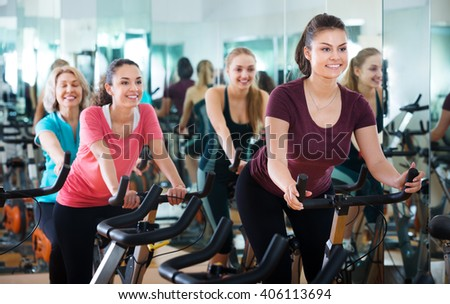 Positive females of different age training on the exercise bikes together in the modern fitness club  - stock photo