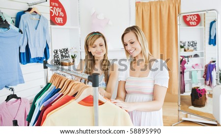 Positive friends choosing colorful clothes in a clothes store together