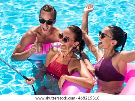 Positive friends having fun in a swimming pool