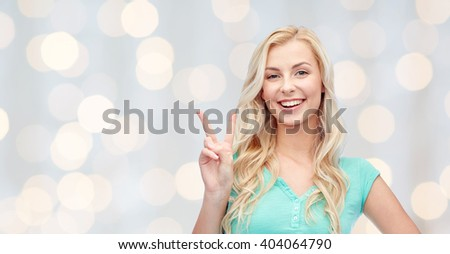 positive gesture and people concept - smiling young woman or teenage girl showing peace hand sign over holidays lights background