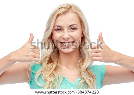 positive gesture and people concept - smiling young woman or teenage girl showing thumbs up with both hands