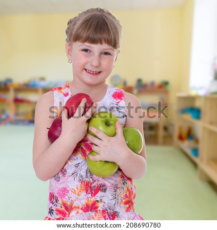 positive girl holding a lot of apples.Summer fun, the concept of happiness and family wellbeing.