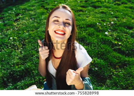 Positive girl shows thumbs up.Happy student in park,sitting on green grass