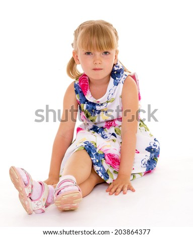 Positive girl sitting on the floor. The white background.