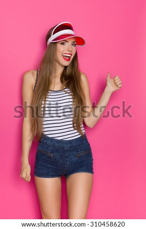 Positive Girl. Smiling young woman in striped shirt and red sun visor showing thumb up. Three quarter length studio shot on pink background. - stock photo