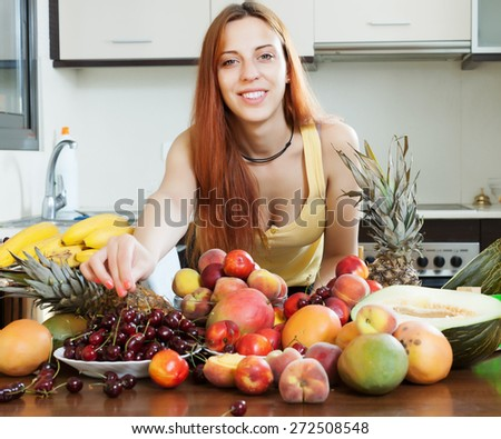 Positive girl with ripe fruits at home kitchen - stock photo