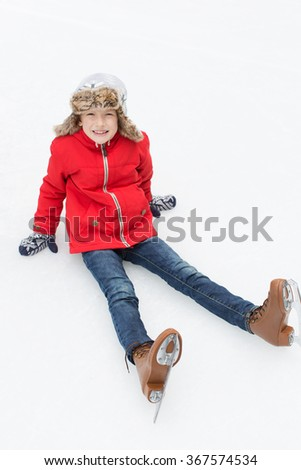 positive happy boy being silly and sitting on ice enjoying winter vacation at outdoor ice skating rink  - stock photo