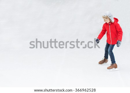 positive happy boy enjoying winter vacation at outdoor ice skating rink learning ice skating - stock photo
