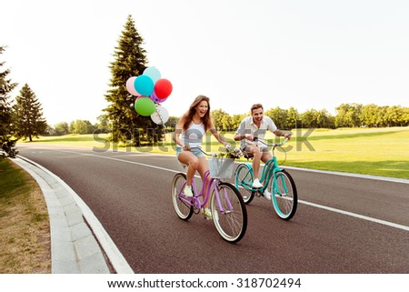 positive happy couple in love ride bicycles have fun - stock photo
