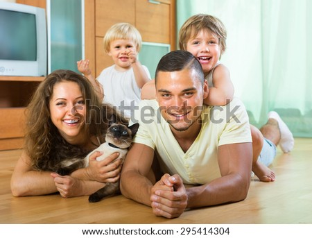 Positive happy family of four laying on the floor with kitten in living room