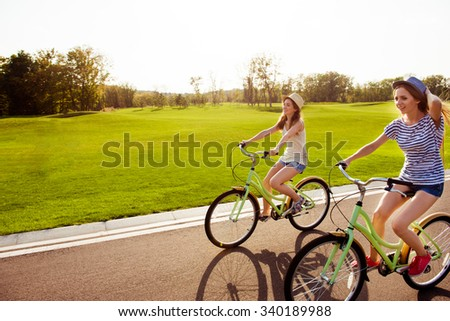 positive happy girls in love ride bicycles and have fun - stock photo