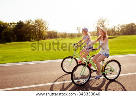 positive happy girls in love ride bicycles on the park - stock photo