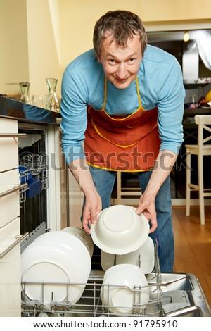 Positive happy housekeeper at kitchen work with dish washing machine - stock photo