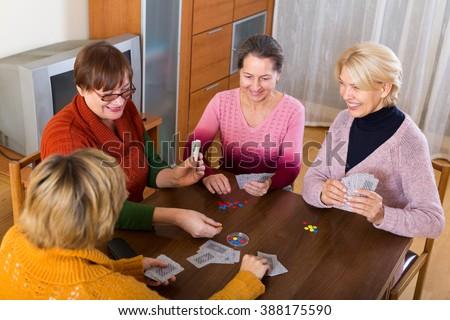 Positive happy senior female friends staking money during bridge - stock photo