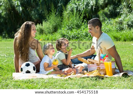 Positive happy smiling family of four on picnic in park at summer day - stock photo