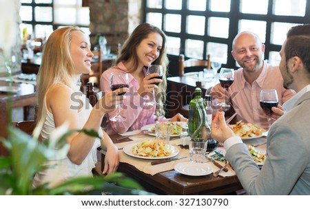 Positive happy young people enjoying food and smiling in tavern  - stock photo