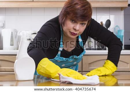 Positive housewife in rubber gloves polishing kitchen tops