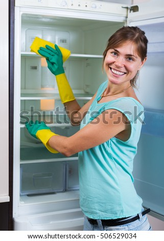 Positive housewife washing fridge with a detergent at a home kitchen