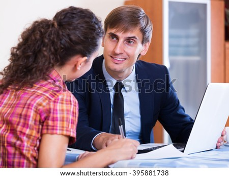 Positive insurance agent and woman customer discussing agreement terms and smiling indoors - stock photo