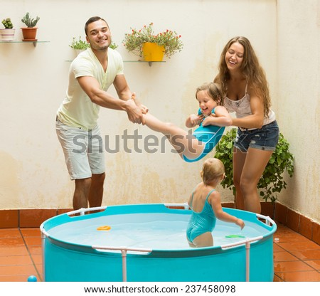 Positive joyful young family of four playing in pool at terrace. Focus on man - stock photo