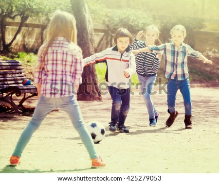 Positive kids playing street football outdoors in spring day