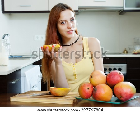 Positive  long-haired woman with mango in home kitchen