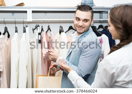 Positive male customer consulting with female shop assistant 