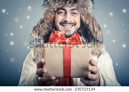 Positive male giving a red ribbon magical giftbox and smiling.  - stock photo