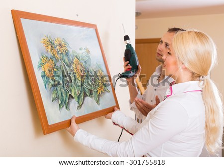 Positive man and woman hanging art picture in frame on the wall. Focus on woman