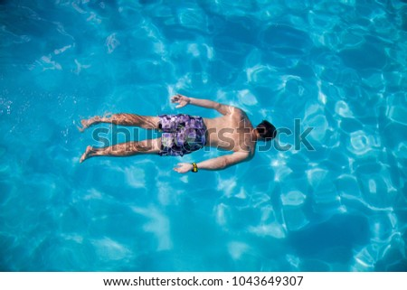 Positive man enjoying in the swimming pool