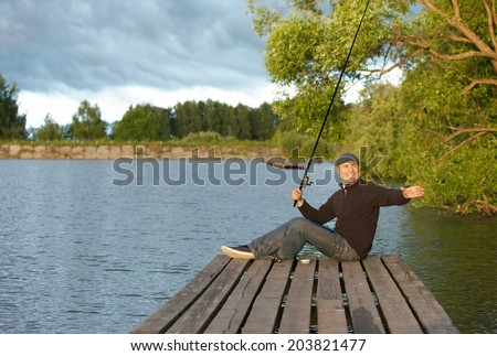 positive man fishing in a pond in a sunny day