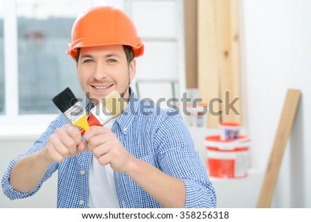 Positive man holding brush  - stock photo