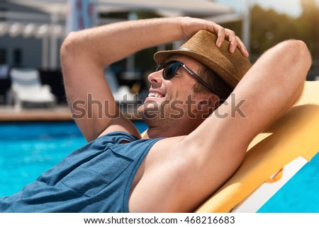Positive man resting near swimming pool