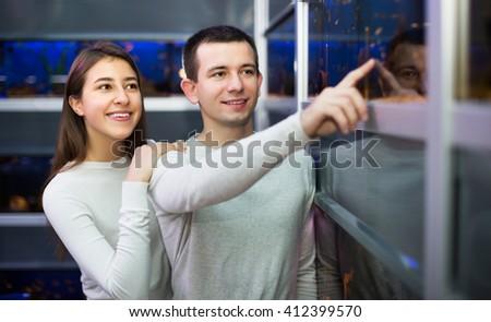 Positive man with young girlfriend choosing aquarium fish in aquarium - stock photo