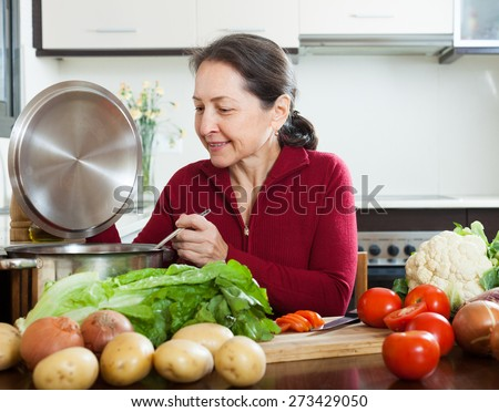 Positive mature woman cooking  with  soup ladle in domestic kitchen