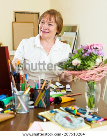 Positive mature woman painting a new picture - stock photo