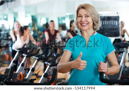 Positive mature woman posing in the modern gym for females
