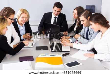 Positive members of the multinational business meetings at work in office. Focus on the right man and woman - stock photo