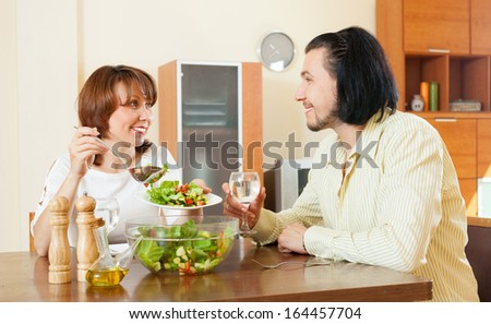 Positive middle-aged woman and man having vegetarian dinner at home  - stock photo