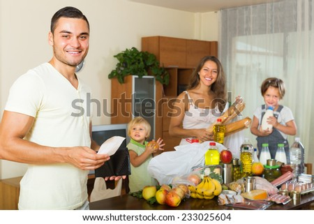 Positive middle-class family of four with bags of food at home  - stock photo
