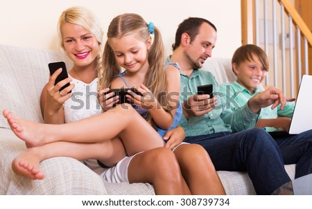Positive mom, dad and two happy kids working with smartphones indoors - stock photo