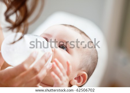 Positive mother feeding her adorable son in the kitchen at home - stock photo