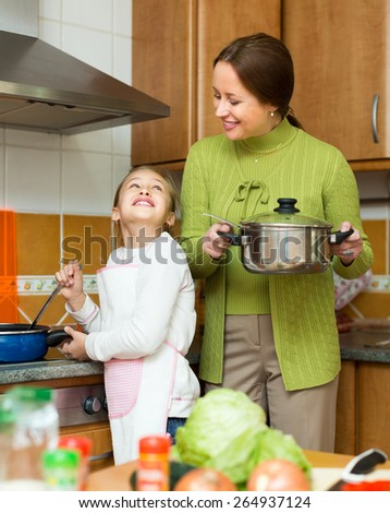 Positive mother with little cheerful daughter cooking at home kitchen and smiling - stock photo