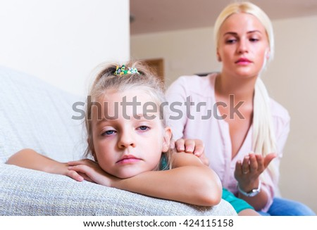 Positive nanny calming a fretful female child at home - stock photo