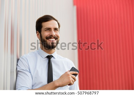 positive office man standing outside with his cellphone and smiling