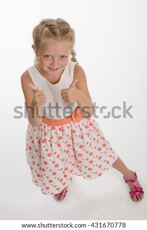 Positive OK gesture of a child shows that everything is going to be OK. Big blue childish fiery eyes look right in the camera. Pleasant smile. - stock photo