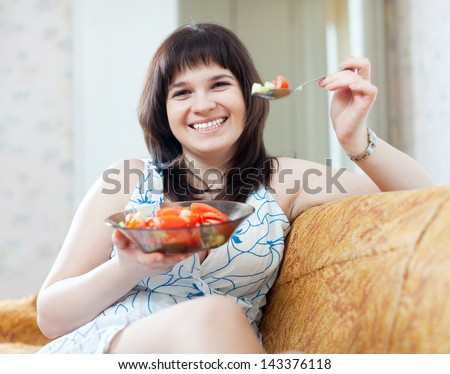 positive ordinary woman eats vegetables salad at home - stock photo