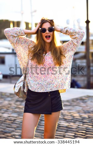 Positive outdoor portrait of stylish hipster blonde woman, casual clothes and sunglasses, positive surprised emotions, evening sunlight, warm colors. - stock photo