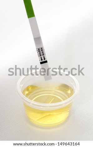 Positive ovulation test in urine cup against white background. - stock photo